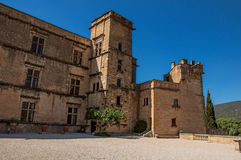 Panoramic of the courtyard and castle facade of Lourmarin. Panoramic of the courtyard and castle facade of Lourmarin with hills in the background, near the Royalty Free Stock Image