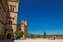 Panoramic of the courtyard and facade of Lourmarin castle. Panoramic of the courtyard and facade of Lourmarin castle with hills in the background, near the Royalty Free Stock Images