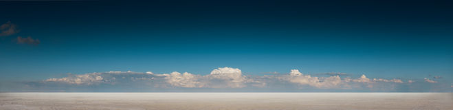 Panoramic desert landscape with deep blue sky and clouds Royalty Free Stock Image