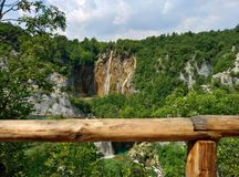 Panoramic distant view on the big waterfall on Plitvice lakes in Croatia. Wooden fence is visible royalty free stock image