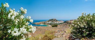 Panoramic view over Lindos village with ruins of ancient Acropolis. Island of Rhodes. Greece. Europe. Panoramic, distant view at Lindos village with ruins of royalty free stock image
