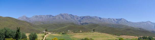 Panoramic farm landscape with high mountains and fields Royalty Free Stock Images