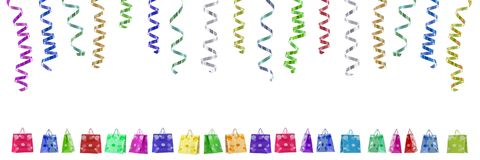 Panoramic festive image with rolls of curly ribbons hanging on top and multi coloured gift bags on the gound on white. Panoramic festive image with rolls of royalty free stock photos