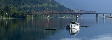 A panoramic of a fishing boat moored in the water. A panoramic image of a small fishing boat moored in the west arm of Kootenay Lake in Nelson, BC Canada Royalty Free Stock Photography