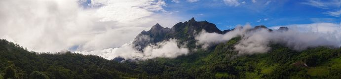 Panoramic. Green mountain scenery There is a mist in the mountains . The sky is blue and the clouds are white.  stock image