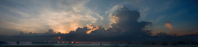 Panoramic hi res combo of sunrise with clouds. 3 files combined to make pannoramic sunrise with majestic clouds and farmland below Royalty Free Stock Photos