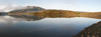 Panoramic of hills reflected in surface of lake foggy morning. Panoramic of hills reflected in surface of lake foggy crisp morning Stock Photo