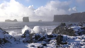 Cape Dyrholaey, Iceland. Panoramic image of the coastal landscape of Cape Dyrholaey on a winter day with snow-covered coastline, Iceland stock footage