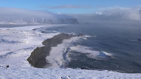 Cape Dyrholaey, Iceland. Panoramic image of the coastal landscape of Cape Dyrholaey on a winter day with snow-covered coastline, Iceland stock video footage