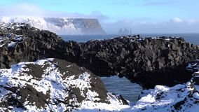 Cape Dyrholaey, Iceland. Panoramic image of the coastal landscape of Cape Dyrholaey on a winter day with snow-covered coastline, Iceland stock video