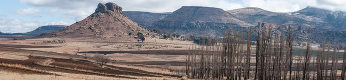 Panoramic image of an Eastern Freestate landscape near Clarens South Africa. Winter landscape South Africa with snowcapped mountains and Prowed lands in Stock Photos
