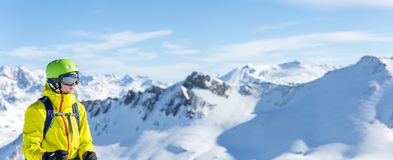 Panoramic image of man in helmet and with snowboard against background of snowy landscape Stock Photos