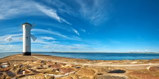 Panoramic image of an old lighthouse in Swinoujscie, a port in P. Oland on the Baltic Sea. The lighthouse was designed as a traditional windmill Royalty Free Stock Images
