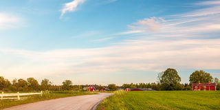 Panoramic image of old wooden farms in Smaland, Sweden. Panoramic image of old red wooden farms with road during sundown in Smaland, Sweden Stock Photo