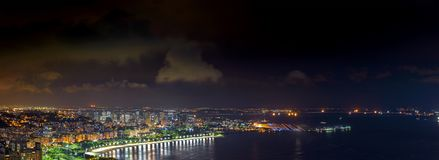 Panoramic image of Rio de Janeiro seen from above at night. With its lights, hills, streets, Gaunabara bay, Rio-Niteroi bridge and Santos Dumont airport Stock Photography