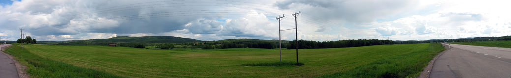 Panoramic image of road though fields. Panoramic shot of a road going beside green fields Stock Image