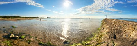 Panoramic image of a seaside with old lighthouse iin Swinoujscie. Panoramic image of a seaside next to lighthouse in Swinoujscie, a port in Poland  on the Baltic Royalty Free Stock Photo