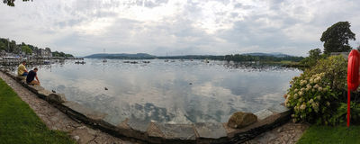 Panoramic Lake WIndermere view with two people seated on promena. Ambleside, England - September 13, 2016: Panoramic view of Lake WIndermere with two people Royalty Free Stock Photos