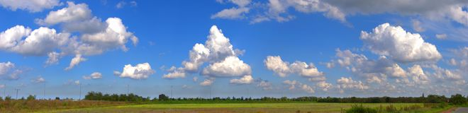 Panoramic landscape with blue sky and puffy clouds. Agricultural summer landscape with blue sky and white puffy clouds. Panorama Royalty Free Stock Photos