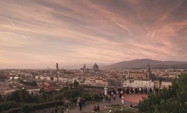 Panoramic landscape of Florence, Italy with a beautiful red sunset and tourists on the viewground stock image