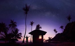 Panoramic landscape of man standing on the coconut beach with a million stars and sunrise. Early morning stock photo