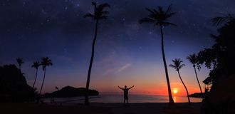 Panoramic landscape of man standing on the coconut beach with a million stars and sunrise. Early morning royalty free stock image