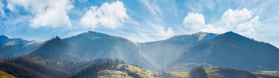 Panoramic landscape of mountainous countryside. In afternoon. gorgeous cloudscape above the ridge. grassy hills and naked trees. mountain tops in snow royalty free stock photography