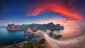 Panoramic landscape with mountains, sea and beautiful sky in sum. Beautiful summer landscape with mountains, sea, blue sky and beautiful colorful red clouds at Royalty Free Stock Photos