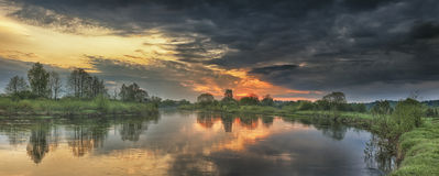 Panoramic landscape of river in autumn morning at sunrise with colorful sky and gray clouds Stock Photos
