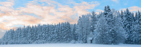 Panoramic landscape of snowbound forest with frosty small church Royalty Free Stock Photography