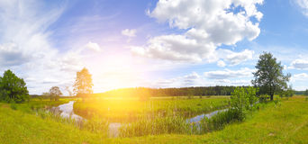 Panoramic landscape of spring morning. Green blossom meadow illuminated by rising sun. Bright sunrise over spring meadow on blue sky background Stock Images