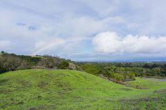 Panoramic landscape view of rainbow after a light rain and deer resting on the hills of Rancho San Antonio county park, south San. Francisco bay, California royalty free stock images