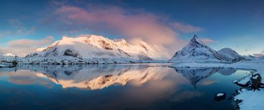 Panoramic landscape, winter mountains and fjord reflection in water. Norway, the Lofoten Islands. stock photos