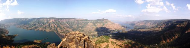 Panoramic and majestic view of river flowing through mountains. Panoramic and majestic view of Koyna river flowing through mountains at Bakalwadi dam in majestic royalty free stock photography