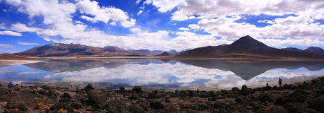 Panoramic Mirrored lake, altiplano, Bolivia. Panoramic photo of a mineral lake, reflecting the licancabur volcano, surrounding mountains and the sky Sbove Stock Photos