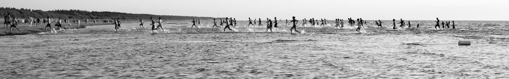 Panoramic monochrome seascape; running people Stock Images