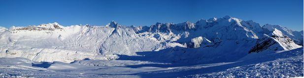 Panoramic Mont Blanc snow view. A panoramic view on Mont Blanc massif of snow mountains from one of the tops over clouds, with many ski tracks on snow. Alpes Stock Images