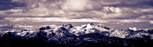 Panoramic Mountain. Panoramic shot of a mountain covered by snow under nice cloudy sky Stock Images