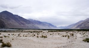 The panoramic mountain ranges of the mighty Himalayas. With white sand deserts of Nubra Valley and patches of greenery Royalty Free Stock Photo