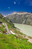 Panoramic mountain road leading to Grimselpass with Grimselsee in Swiss Alps Stock Images