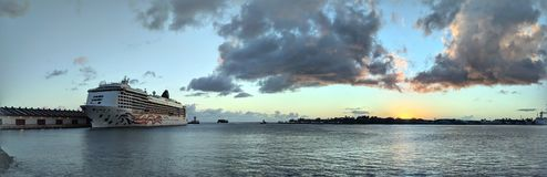 Panoramic of NCL Pride of America Cruise ship docked in Honolulu Harbor at Sunset. Honolulu- November 3, 2018: Panoramic of NCL Pride of America Cruise ship royalty free stock photo