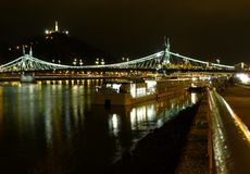 Night view of brightly lit Liberty bridge in Budapest. Panoramic night view of brightly lit Liberty bridge in Budapest over the calm Danube river with stock photos