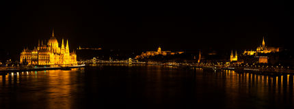 Panoramic night view on Hungarian Parliament Building located at the bank of the Dunabe river with famous Chain Bridge connecting Stock Photos