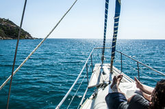 Panoramic ocean and landscape shot front of the yacht in summer time in italy sardinia with girl Stock Photography