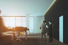 Panoramic open space office front toned. Modern gray wall open space office interior with a gray floor, rows of computer tables and white doors. Business people Royalty Free Stock Image