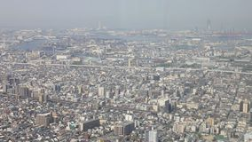 Panoramic Osaka cityscape. Aerial view time lapse of Osaka skyline from observation deck of platform of Osaka`s Abeno Harukas, tallest skyscraper in Japan. Sunny stock footage