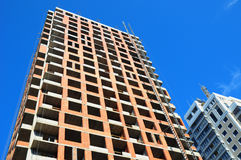 Panoramic and perspective wide angle view to high-rise building under construction exterior. The site building construction facade walls against blue sky Royalty Free Stock Photography
