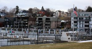 Panoramic photo of a lake town during winter. Lake house new buildings, with view of the marina and cold frozen lake Royalty Free Stock Photography