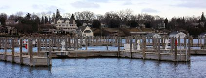 Panoramic photo of a lake town during winter. Lake house new buildings, with view of the marina and cold frozen lake Royalty Free Stock Image