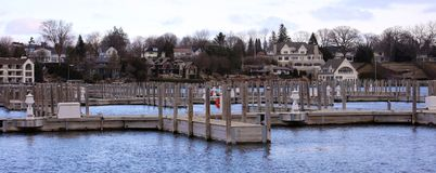 Panoramic photo of a lake town during winter. Lake house new buildings, with view of the marina and cold frozen lake Stock Photography